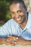 Happy African American Man Smiling. A happy African American man sitting outside and smiling with perfect white teeth Royalty Free Stock Photography