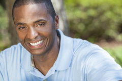 Happy African American Man Smiling. A happy African American man sitting outside and smiling with perfect white teeth Royalty Free Stock Photos