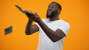 Happy African-American man throwing dollars banknotes, wasting money, concept. Stock footage stock footage