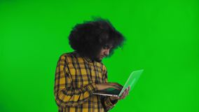 Happy African American man using laptop on green screen or chroma key background. Concept of emotions. 4K stock video