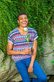Happy African American Man with white rose waiting for you at Ce. Happy Man. Wearing a short sleeve, collarless, colorful pattern shirt, blue jeans, a young Royalty Free Stock Photography