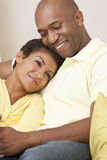 Happy African American Man & Woman Couple. A happy African American man and woman couple in their thirties sitting at home together smiling royalty free stock image