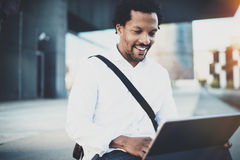 Happy African American man working with electronic touch pad pro with holding in hands.Concept of guy using Internet Stock Photography