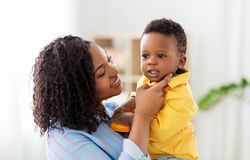 Happy african american mother with baby at home. Childhood, kids and people concept - happy african american mother with her baby son at home stock images