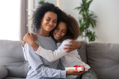 Happy mom hugging daughter thanking for present stock photo