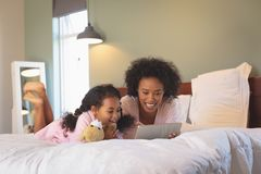 Happy African American mother and her daughter using digital tablet royalty free stock images