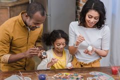 African american parents and daughter painting easter eggs. Happy african american parents and daughter painting easter eggs Royalty Free Stock Photography