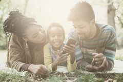 Happy African American parents in park with daughter using mobil stock images