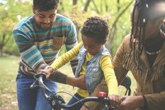Happy African American parents teaching their little girl to driving bike in park. stock photos