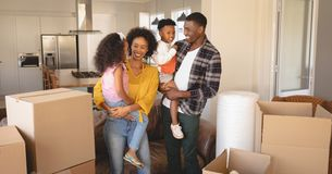 Happy African American parents with their children and boxes moving in new house stock photography