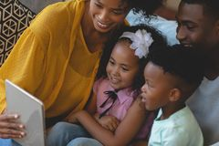 Happy African American parents with their cute children using digital tablet on sofa. Front view of happy African American parents with their cute children using royalty free stock photography