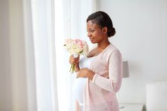 Happy african american pregnant woman with flowers stock photo