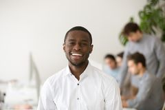 Happy african-american professional manager smiling looking at c. Happy african american professional smiling looking at camera with colleagues at background royalty free stock photography