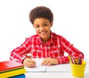 Happy African American school boy taking test stock photos