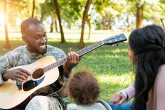 Happy african american soldier in military uniform playing guitar for family. In park royalty free stock photography