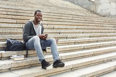 African-american student sitting on stairs and using his smartphone outdoors. Happy african-american student sitting on stairs and listening to music on his Stock Images