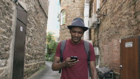 Happy african american student walking and using smartphone app outdoors stock video footage