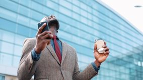 Happy African American successful businessman gets great news on smartphone. He stands near an office center. Smartphone. App concept stock footage