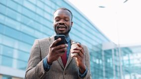 Happy African American successful businessman gets great news on smartphone. He stands near an office center. Smartphone. App concept stock video footage