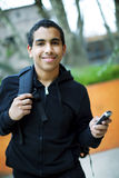 Happy african american teen boy with mobile phone. Happy african american student with with mobile phone Royalty Free Stock Photos