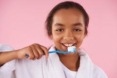 Happy African American teen girl brushes teeth. stock photos