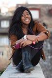 Happy african american teenage girl listenin Royalty Free Stock Image