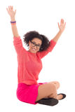 Happy african american teenage girl in pink sitting isolated  Royalty Free Stock Photos