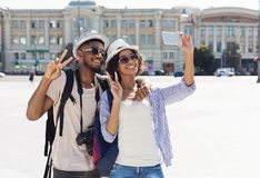 Happy african-american tourists taking selfie in new city. Copy space stock images