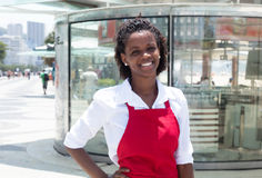 Happy african american waitress in front of the restaurant. With modern bar in the background Stock Image