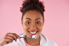 Happy African American woman brushes teeth. royalty free stock photography