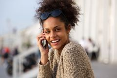 Happy african american woman calling by cellphone outdoors Stock Images