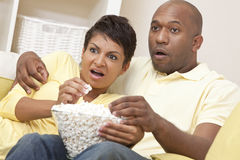 Happy African American Woman Couple Eating Popcorn. A happy African American men and women couple in their thirties sitting at home, eating popcorn and looking Royalty Free Stock Image
