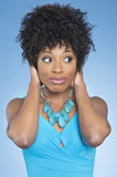 Happy African American woman covering ears over while looking away colored background Stock Image