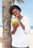 Happy african american woman drinking coconut water Royalty Free Stock Images