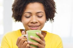Happy african american woman drinking from tea cup. People, drinks and leisure concept - happy african american woman drinking tea from cup or mug at home Royalty Free Stock Photos