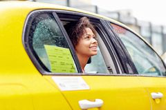 Happy african american woman driving in taxi Stock Photos