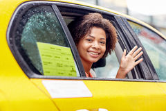 Happy african american woman driving in taxi Stock Photo