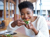 Happy african american woman eating pizza Stock Photos