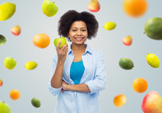 Happy african american woman with green apple Stock Images