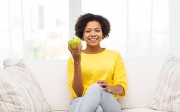 Happy african american woman with green apple Royalty Free Stock Images