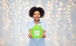 Happy african american woman with green house icon Stock Photos