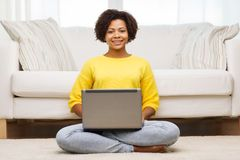 Happy african american woman with laptop at home Royalty Free Stock Images