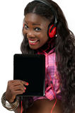 Happy African American woman listening to music wi. Portrait of a happy African American woman listening to music with headphone attached to tablet PC royalty free stock images