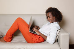 Happy african american woman with notebook on couch Stock Images