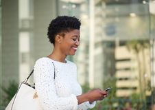 Happy african american woman reading text message Royalty Free Stock Photos