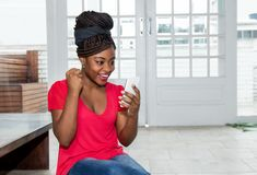 Happy african american woman receiving good news on phone royalty free stock photos