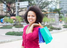 Happy african american woman with shopping bags in the city Stock Photos