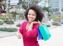 Happy african american woman with shopping bags showing thumb Royalty Free Stock Image