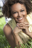 Happy African American Woman Smiling Outside. Beautiful young mixed race black African American woman with perfect teeth smiling and relaxing laying down on Stock Image
