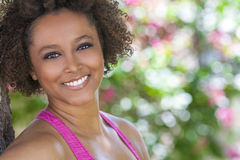 Happy African American Woman Smiling Outside. Beautiful young mixed race black African American woman with perfect teeth smiling and relaxing outside in summer Stock Photo